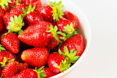 Röda nya jordgubbar i en bunke som isoleras på vit bakgrund Slapp fokus Royaltyfri Foto