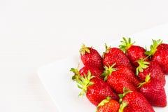 Röda nya jordgubbar i en vit maträtt som isoleras på vit bakgrund Slapp fokus Royaltyfria Foton