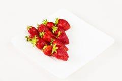 Röda nya jordgubbar i en vit maträtt som isoleras på vit bakgrund Slapp fokus Arkivbild