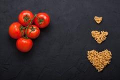Röda nya tomater och svart för pastahjärtaform hårdnar backgrou Royaltyfri Foto