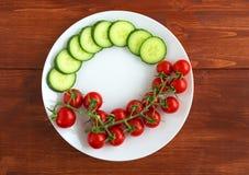 Röda nya tomater på en vit platta och en skivad gurka Arkivbild