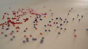 Röda och blåa pärlor på en ljus bakgrund Royaltyfria Bilder