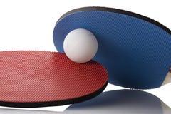 Röda och blåa Ping Pong Paddles - boll in - between Arkivfoto