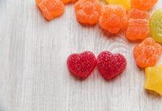 Röda och färgrika godisar för hjärtaformgelé Trävit bordlägger Sp Royaltyfria Bilder