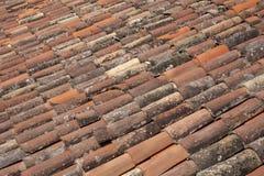 Röda och gamla tegelplattor på ett tak arkivbild