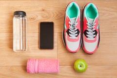 Röda och gråa gymnastikskor med gråa skosnöre och den röda handduken, det gröna äpplet, flaska med vatten, mobiltelefon med vit h Arkivbild