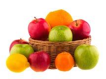 Röda och gröna äpplen, apelsiner och citroner i en träkorg fotografering för bildbyråer