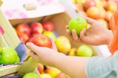 Röda och gröna äpplen för kvinnainnehav i supermarket Grönsaker och frukter i bakgrunden ben för bakgrundspåsebegrepp som shoppar Royaltyfri Fotografi