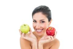 Röda och gröna äpplen för lyckligt brunettinnehav och se camer Fotografering för Bildbyråer