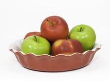 Röda och gröna äpplen i en pajplatta Arkivbilder