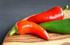 Röda och gröna chili på trä och kritiserar bakgrund Arkivbild
