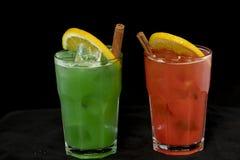 Röda och gröna coctailar med den röda och gröna fruktsaft-, alkohol- och limefruktkilen royaltyfria foton