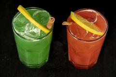 Röda och gröna coctailar med den röda och gröna fruktsaft-, alkohol- och limefruktkilen fotografering för bildbyråer