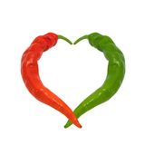 Röda och gröna förälskade chilipeppar Fotografering för Bildbyråer