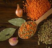 Röda och gröna linser med kryddor på träbakgrunden Royaltyfri Foto