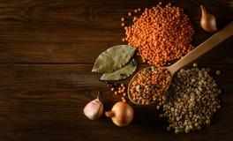 Röda och gröna linser med kryddor på träbakgrunden Arkivfoto