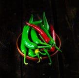 Röda och gröna varma Chili Peppers i bunke Royaltyfri Foto