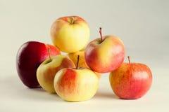 Röda och gula äpplen på den tonade retro bakgrunden Arkivbilder