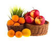 Röda och gula äpplen, tangerin och citroner i en träkorg Royaltyfri Foto