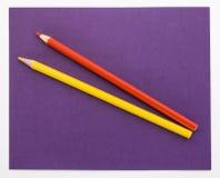 Röda och gula blyertspennor på en purpurfärgad bakgrund Royaltyfria Bilder