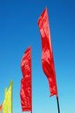 Röda och gula flaggor blå sky för bakgrund Arkivbild