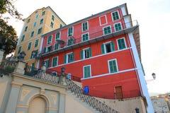Röda och gula hus med gröna slutare i Korsika arkivfoton