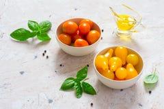 Röda och gula körsbärsröda tomater i en bunke Arkivbilder