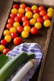 Röda och gula körsbärsröda tomater i träask Arkivfoto