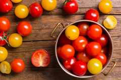 Röda och gula körsbärsröda tomater på träbakgrund Arkivbild