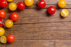 Röda och gula körsbärsröda tomater på träbakgrund Arkivbilder