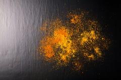 Röda och gula kryddor på en svart bakgrund Selektivt fokusera CU Arkivbild