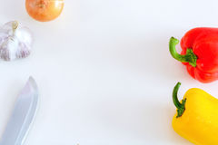 Röda och gula peppar, lök, vitlök och kniv på en vit bakgrund, bästa sikt Royaltyfri Fotografi