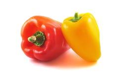Röda och gula peppar på en tabell med en vit bakgrund Arkivfoto