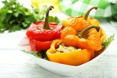 Röda och gula peppar som är välfyllda med köttet, risen och grönsakerna Arkivfoto