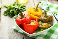 Röda och gula peppar som är välfyllda med köttet, risen och grönsakerna Royaltyfri Bild