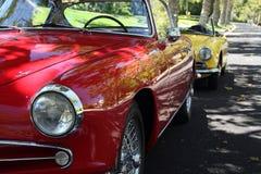 Röda och gula tappningbilar royaltyfria foton