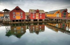 Röda och gula trähus i norsk by Royaltyfri Bild