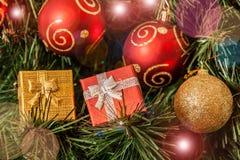 Röda och guld- bollar och gåvor för Ñ-hristmas Selektiv fokus på gåvor Royaltyfria Foton
