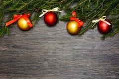 Röda och guld- julbollar på gran förgrena sig på mörk träbakgrund, kopieringsutrymme, bästa sikt royaltyfri fotografi
