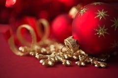 Röda och guld- julprydnader på röd bakgrund Fotografering för Bildbyråer
