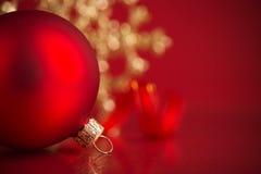Röda och guld- julprydnader på röd bakgrund med kopieringsutrymme Royaltyfria Bilder