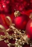 Röda och guld- xmas-prydnader på ljus bokehbakgrund Royaltyfri Fotografi