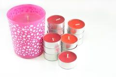 Röda och rosa färgstearinljus på vit bakgrund Fotografering för Bildbyråer
