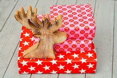 Röda och rosa gåvor för jul för stjärnablommamodell med träreindeeron en trähyllabakgrund Royaltyfri Fotografi