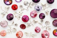 Röda och rosa kristaller och metallbin och blommor och sländor på vit bakgrund Royaltyfri Fotografi