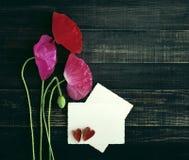 Röda och rosa poppys och vitt kort med inskriften och två dekorativa hjärtor Arkivfoton