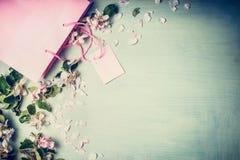Röda och rosa shoppingpåsar med sommar eller vårblommor och sidor på en ljus mintkaramellbakgrund, en bästa sikt, en ramvår eller royaltyfri fotografi