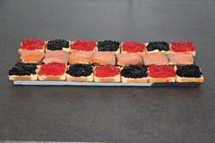 Röda och svarta ägg av klumpa sig och laxrostade bröd Arkivfoton