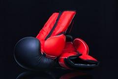 Röda och svarta boxninghandskar på det svarta glass skrivbordet Royaltyfri Fotografi