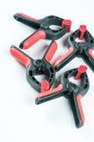 Röda och svarta plast- snickare klämmer hjälpmedel plana lägger ovanför vit bakgrund Arkivfoto